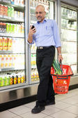 Hombre con cesta de abarrotes y teléfono móvil — Foto de Stock