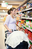 Mother with Carriage in Supermarket — Stock Photo