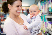 Cheerful mother and baby in shopping centre — Foto de Stock