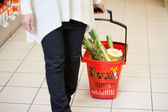 Kobieta w supermarkecie ciągnąc kosz — Zdjęcie stockowe