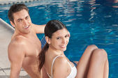 Beautiful young couple relaxing by the poolside — Stock Photo