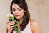 Pretty young woman holding a white rose — Stock Photo