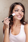 Young woman applying cosmetic paint brush — Stock Photo