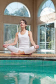 Woman meditating sitting in lotus position — Stock Photo
