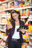 Woman looking at a product while holding digital tablet in shopp — Stock Photo