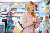 Jovem mulher segurando jar no supermercado — Foto Stock