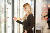 Woman Buying Juice from Cooler — Stock Photo
