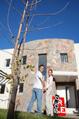 Happy couple in front of their new home — Stock Photo