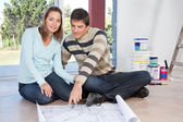 Couple sitting on the floor with blueprint of their new house — Foto de Stock