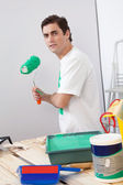 Casual man holding a roller paint brush — Stock Photo