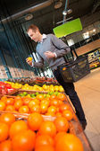 Mannen i supermarket köpa frukt — Stockfoto