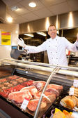 Fresh meat with cheerful butcher — Stock Photo