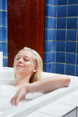 Young relaxed blond woman in a bathtub — Stock Photo