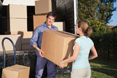 Couple carrying box into the truck — Stock Photo