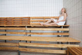 Young blond woman relaxing in sauna — Stock Photo