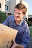 Portrait of smiling man holding box — Stock Photo