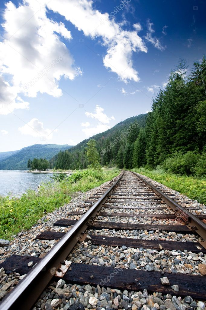 Train tracks near a large lage going through the mountains  Stock Photo #5730558