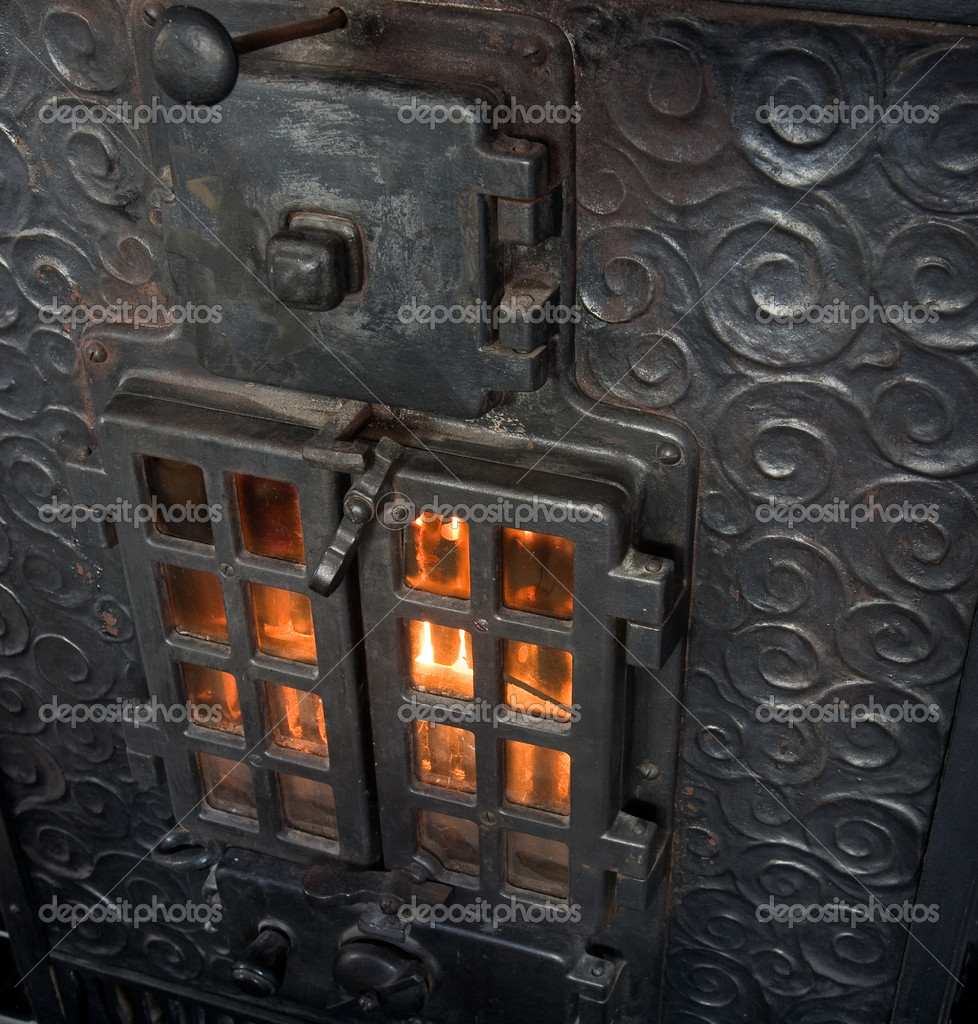 An old cast iron oven with flames viewable through the window — Stock Photo #5732785