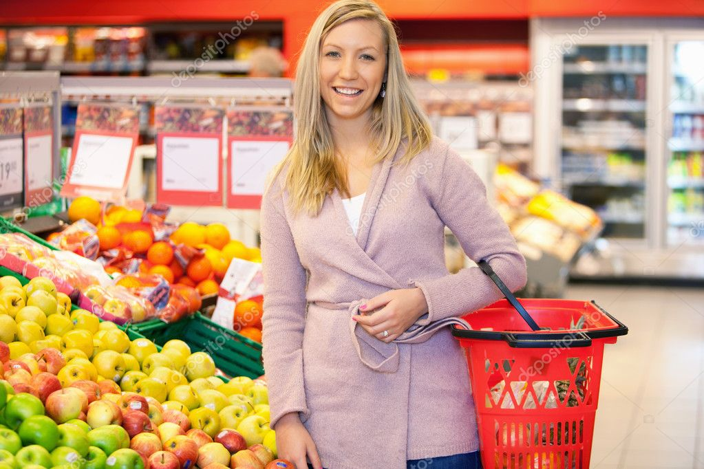 Portrait of a young woman smiling while buying fruits in the supermarket  Stock Photo #5732978