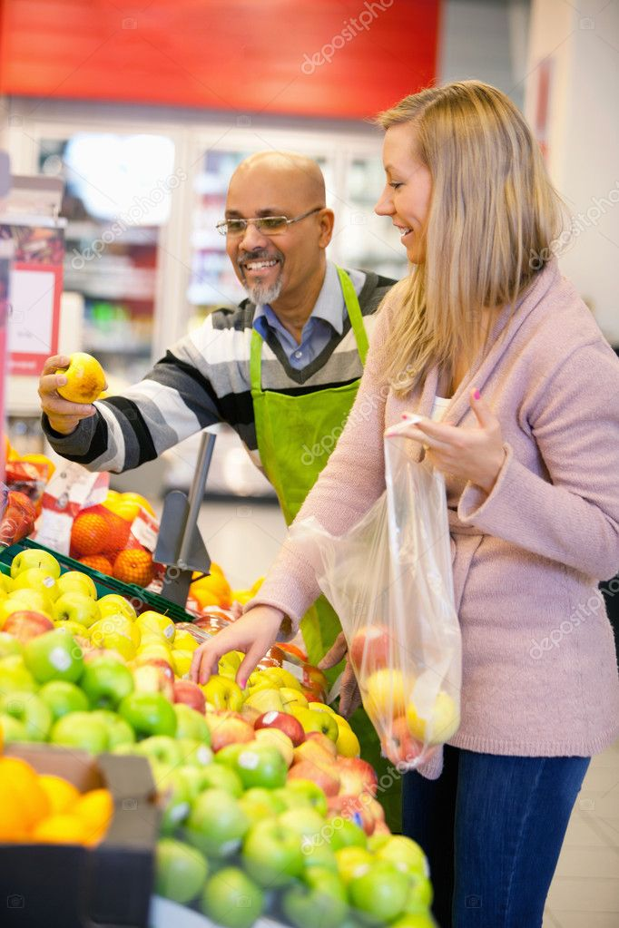 Happy young woman buying fruits with shop assistant in the background — Stock Photo #5734715