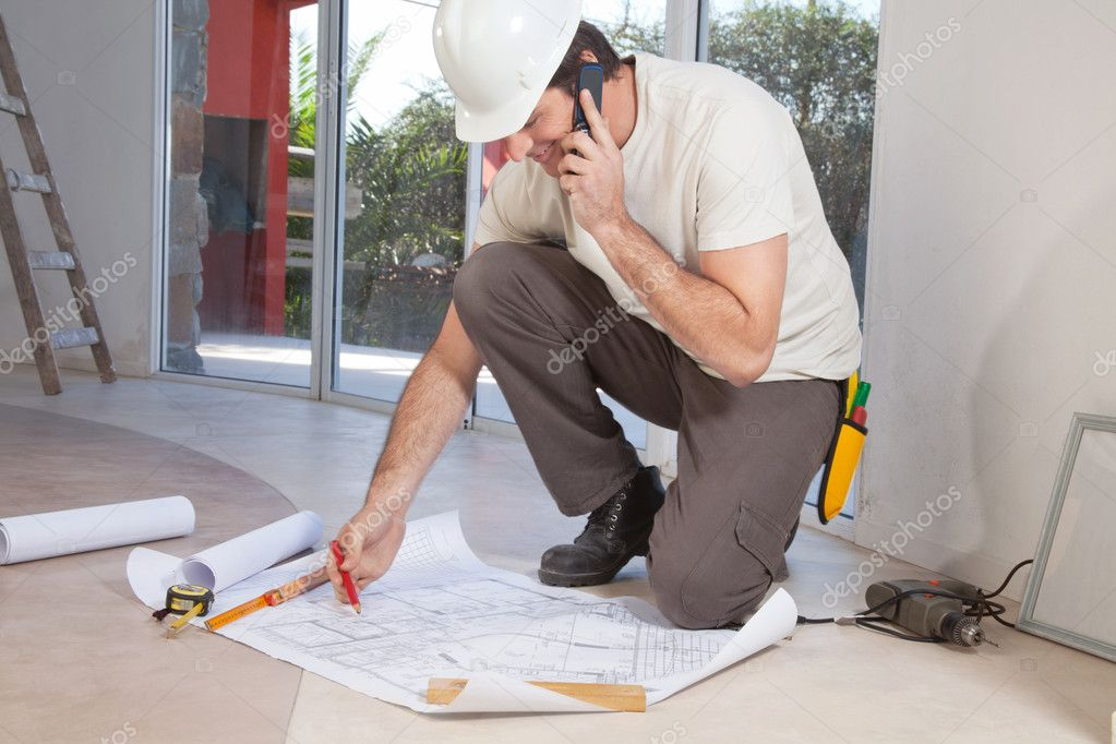 Construction worker working on blueprint and talking on cellphone — Stock Photo #5734835