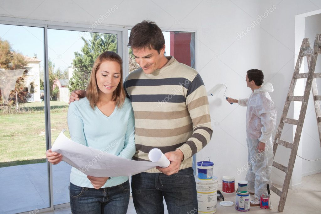 Couple going through house plan while painter in the background — Stock Photo #5734965