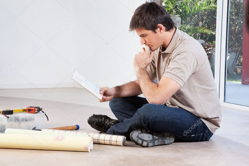 Mature man going through the color swatch while sitting on the floor — Stock Photo #5735009