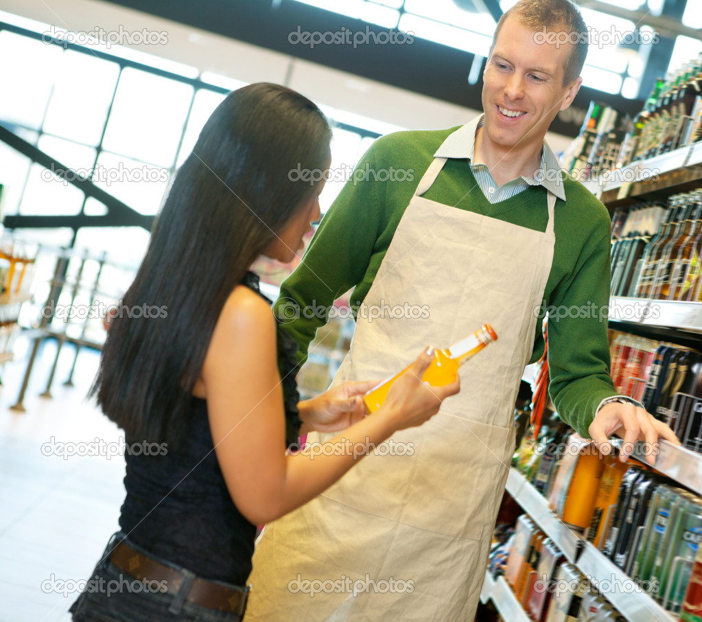 helpful grocery store clerk stock photo copy simplefoto  w standing smiling store worker while holding drink bottle in grocery store photo by simplefoto
