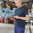 Stock Photo: Yong mechanic with digital tablet