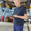 Yong mechanic with digital tablet - Stock Photo