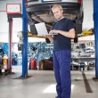 Stock Photo: Portrait of smiling mechanic working on laptop