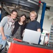 Couple standing with mechanic using laptop — Stock Photo #6478476