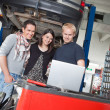 Couple standing with mechanic using laptop — Stock Photo