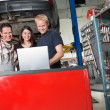 Foto Stock: Smiling couple standing with mechanic using laptop