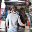 Rear view of young couple in garage - Stock Photo