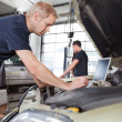 Mechanic using laptop while working on car — Foto Stock