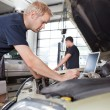 Mechanic using laptop while working on car - Stockfoto