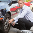 Business Man Replacing Tire - Stock Photo