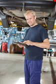 Yong mechanic with digital tablet — Stock Photo