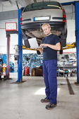 Portrait of smiling mechanic working on laptop — Stock Photo