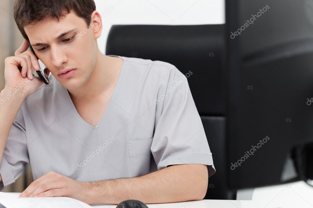 Serious young dentist having conversation on mobile phone — Stock Photo #6477899