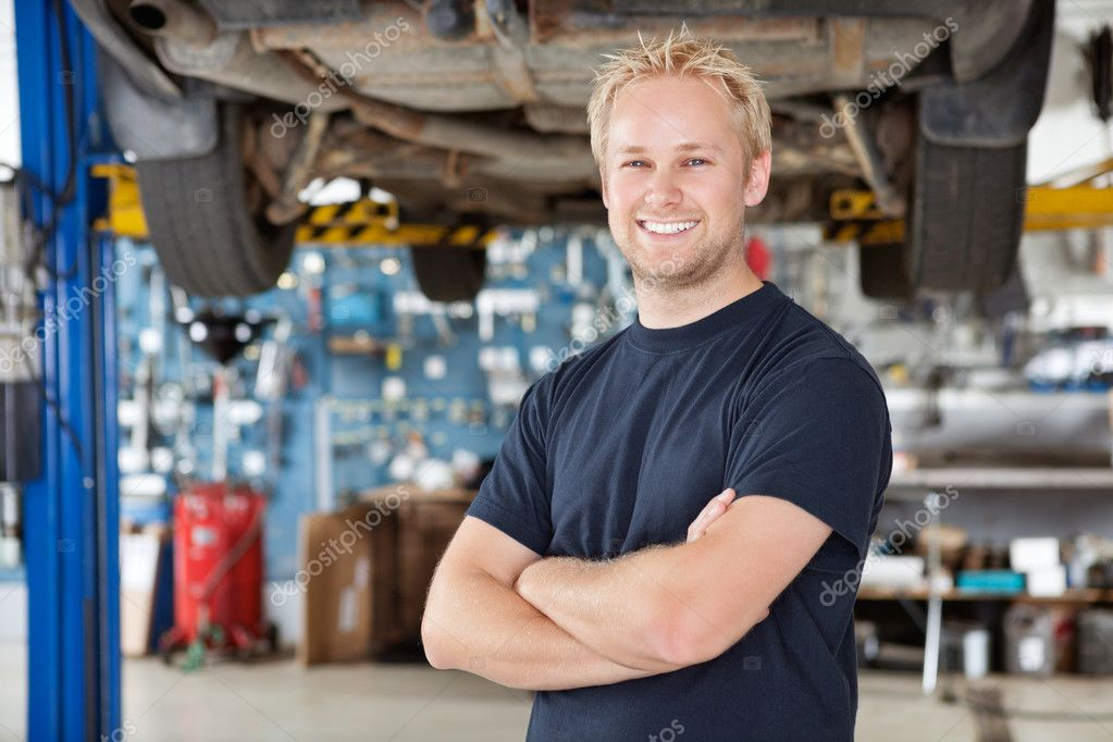 Portrait of cheerful young mechanic with arms crossed standing in his auto repair shop — Stock Photo #6477997