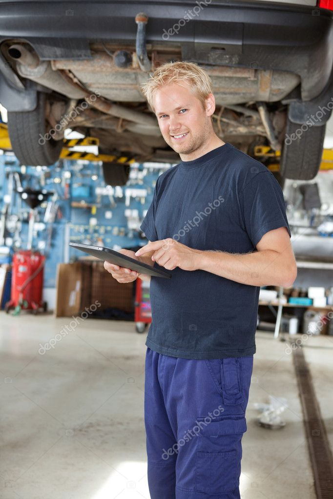 Portrait of young mechanic standing and using digital tablet in his auto repair shop — Stock Photo #6478044