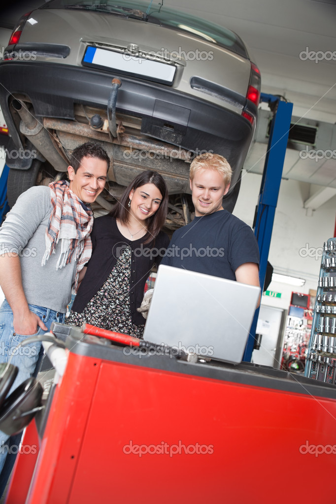 Smiling young couple standing with mechanic using laptop in auto repair shop — Stock Photo #6478476