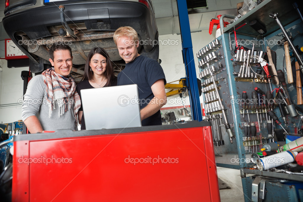 Young smiling couple standing with mechanic using laptop in auto repair shop — Stock Photo #6478510