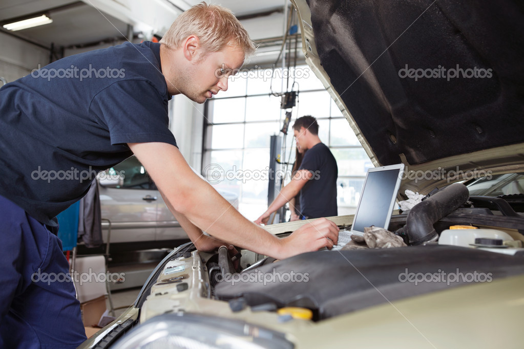 Mechanic using laptop while working on car with in background — Stok fotoğraf #6479196