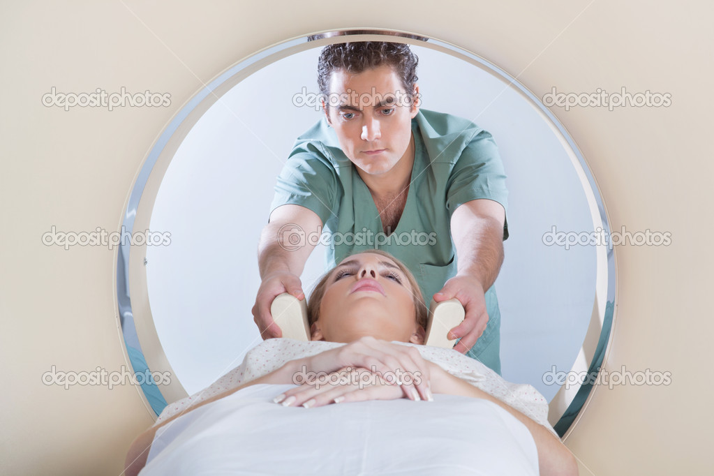 Nurse preparing young woman for CT scan test  Stock Photo #6529955