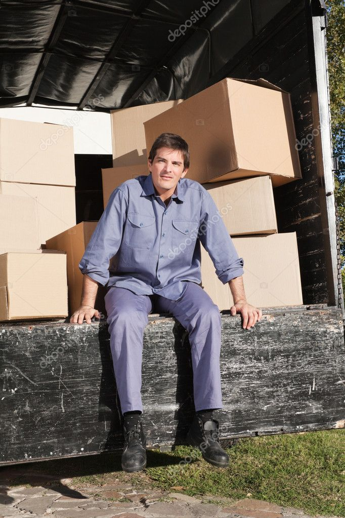 Thoughtful man sitting in the truck with pile of boxes behind him — Stock Photo #6531575