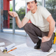 Construction worker with project paper - Stock Photo