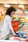 女人购买封冻在超市里的食品 — 图库照片